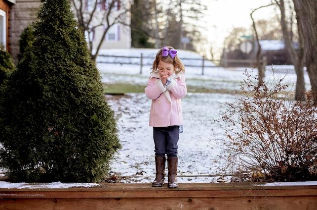 Kleines mädchen, das auf holzbrettern in einem garten steht, der im schnee bedeckt ist und unter sonnenlicht betet