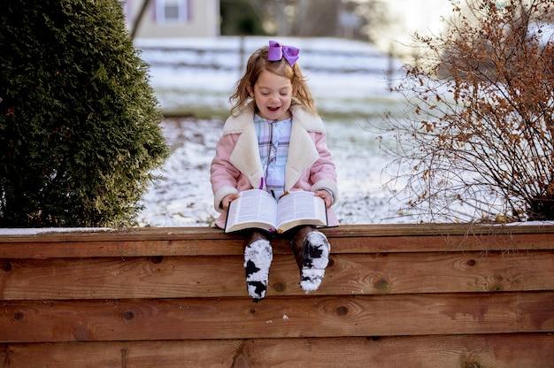 Kleines mädchen, das auf holzbrettern sitzt und die bibel in einem garten liest, der mit dem schnee bedeckt ist