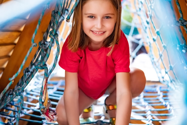Kleines mädchen, das auf kletternetz auf parkspielplatz spielt