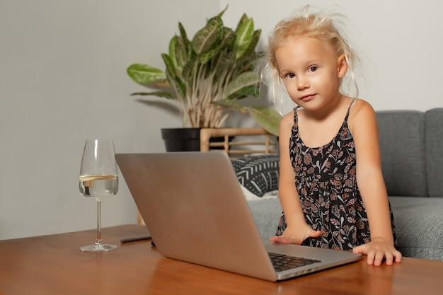 Kleines mädchen, das auf laptop spielt. hochwertiges foto