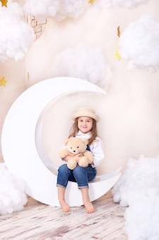 Kleines mädchen, das auf mond mit wolken mit einem teddybär in ihren händen sitzt und spielt.