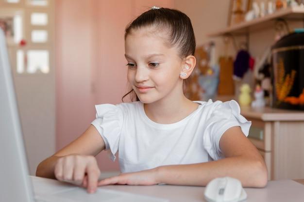 Kleines mädchen, das auf online-lektionen achtet