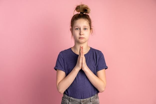 Kleines mädchen, das auf rosa wand betet