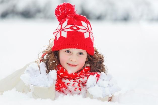 Kleines mädchen, das auf schnee liegt.