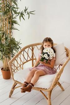 Kleines mädchen, das auf sessel mit blumenstrauß der frühlingsblumen sitzt