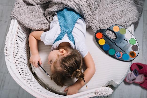 Kleines mädchen, das auf sofa mit aquarellpalette schläft