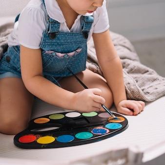 Kleines mädchen, das auf sofa mit aquarellpalette sitzt