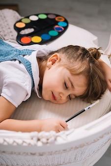 Kleines mädchen, das auf sofa mit heller aquarellpalette schläft