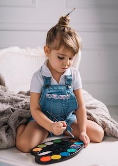 Kleines mädchen, das auf sofa mit heller aquarellpalette sitzt