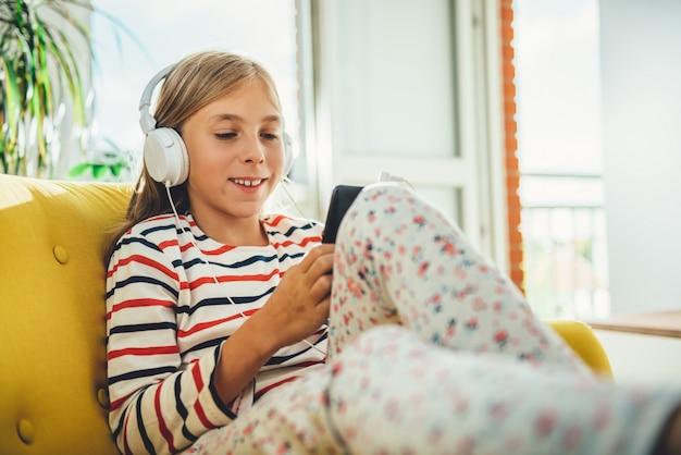 Kleines mädchen, das auf sofa sitzt und intelligentes telefon verwendet
