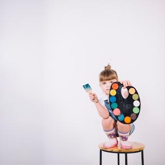 Kleines mädchen, das auf stuhl mit palette und pinsel sitzt