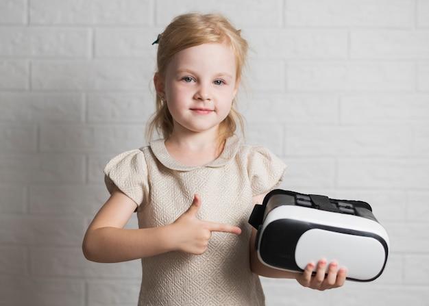 Kleines mädchen, das auf virtuellen kopfhörer zeigt