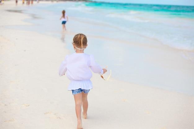 Kleines mädchen, das auf weißem sandigem strand in mexiko läuft