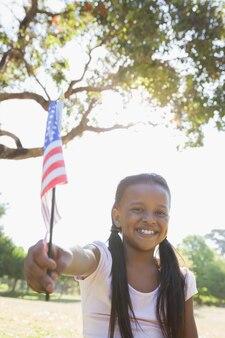 Kleines mädchen, das auf wellenartig bewegender amerikanischer flagge des grases an einem sonnigen tag sitzt