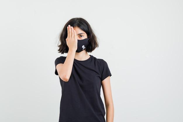 Kleines mädchen, das auge mit hand im schwarzen t-shirt, maske, vorderansicht bedeckt.
