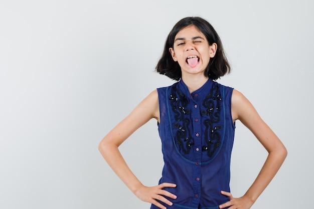 Kleines mädchen, das auge zwinkert und zunge in blauer bluse herausstreckt