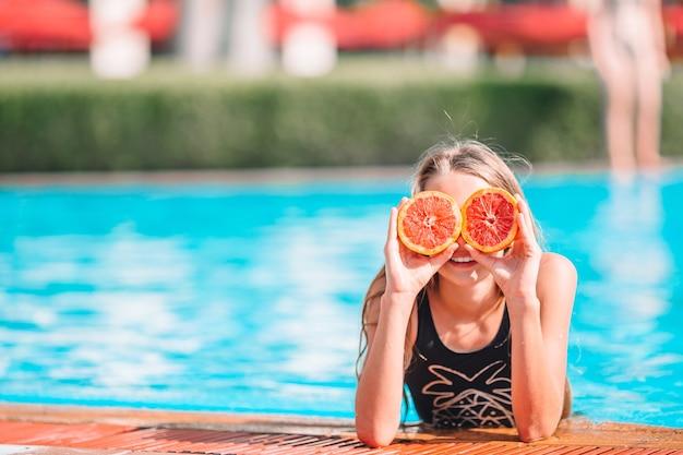 Kleines mädchen, das augen mit orangefarbenen hälften nahe augen auf hintergrundschwimmbad bedeckt