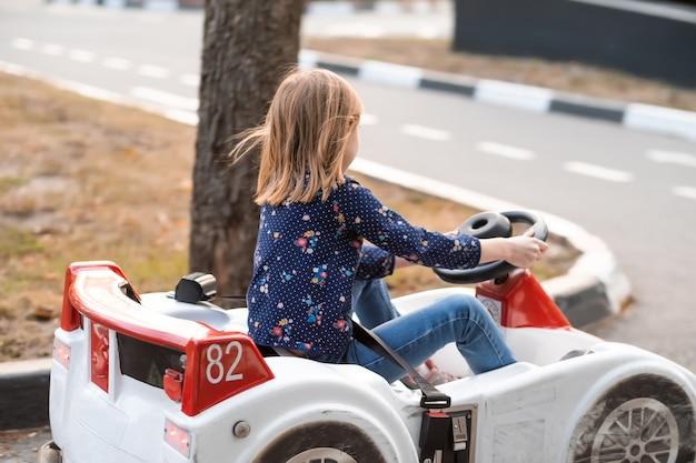 Kleines mädchen, das auto auf kinderstraße im abenteuerpark fährt