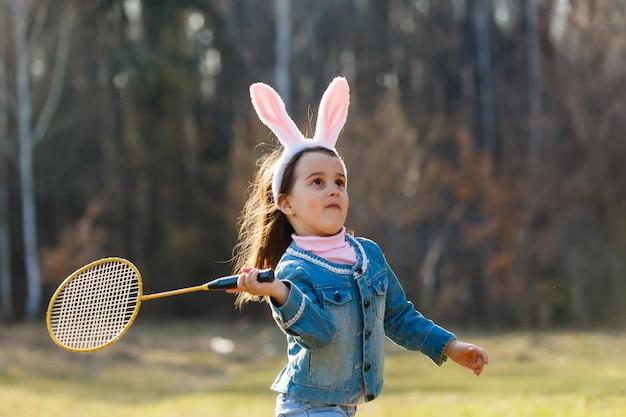 Kleines mädchen, das badminton in der wiese spielt