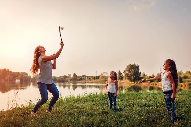 Kleines mädchen, das badminton mit schwester im sommerpark spielt