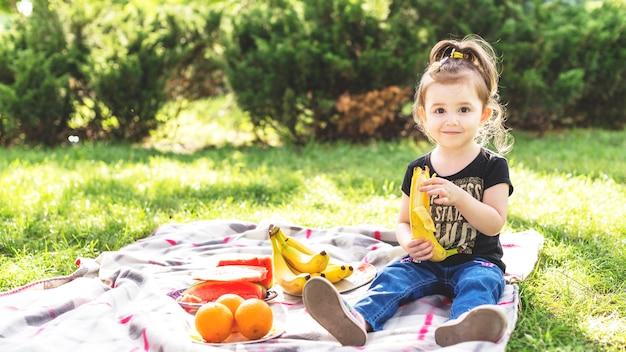 Kleines mädchen, das banane am picknick im park isst