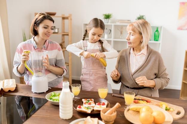 Kleines mädchen, das banane schält, während es ihrer mutter und oma mit fruchtsmoothie zum frühstück hilft