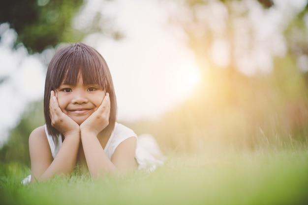 Kleines mädchen, das bequem auf dem gras und dem lächeln liegt
