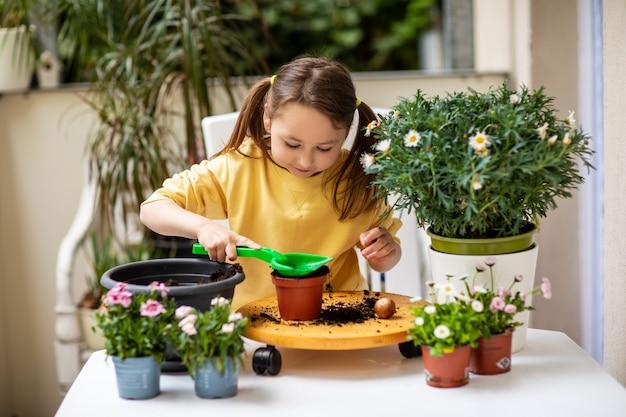 Kleines mädchen, das blumen auf dem balkon pflanzt und sich um pflanzen kümmert