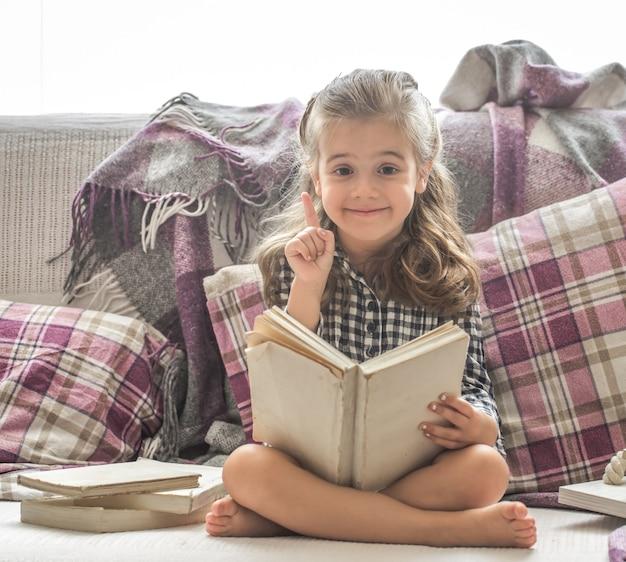 Kleines mädchen, das buch auf sofa liest