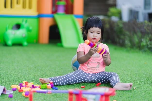 Kleines mädchen, das bunte plastikblöcke des spielzeugs im spielplatz spielt