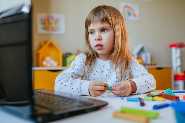 Kleines mädchen, das bunten ton formt, der online-lernstunde auf dem laptop innen beobachtet