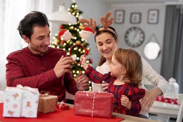 Kleines mädchen, das darauf wartet, weihnachtsgeschenke zu öffnen