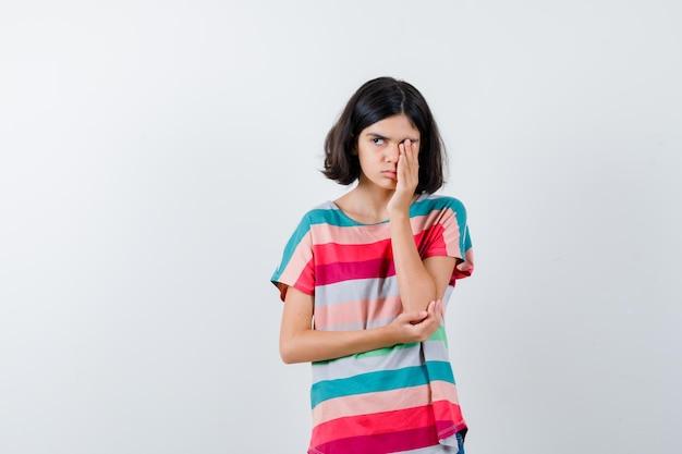 Kleines mädchen, das das auge mit der hand bedeckt, während es die hand am ellbogen hält, im t-shirt wegschaut und schläfrig aussieht, vorderansicht.