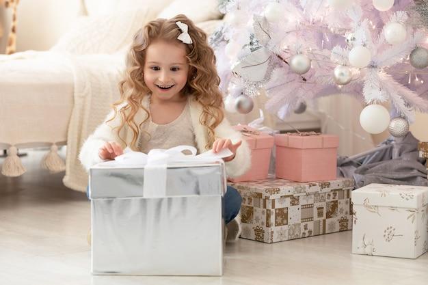 Kleines mädchen, das das geschenk unter dem weihnachtsbaum öffnet.