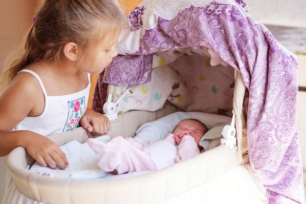 Kleines mädchen, das das neugeborene baby in der krippe betrachtet