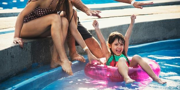 Kleines mädchen, das das pool auf einem sommerschwimmen genießt