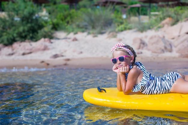 Kleines mädchen, das das schwimmen im gelben kajak im klaren türkiswasser genießt
