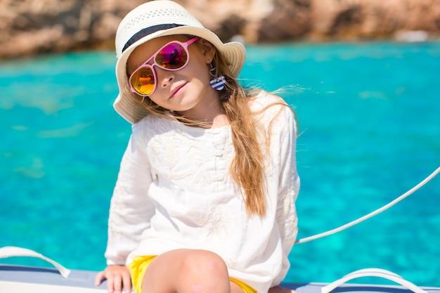 Kleines mädchen, das das segeln auf boot im offenen meer genießt