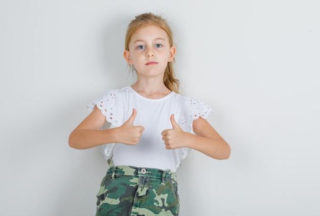 Kleines mädchen, das daumen hoch im weißen t-shirt zeigt