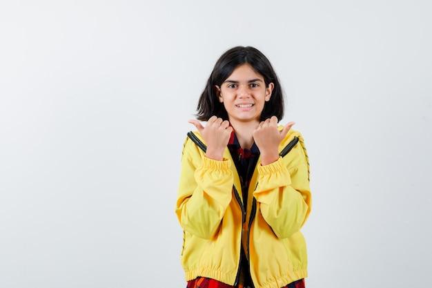 Kleines mädchen, das daumen oben im karierten hemd, in der jacke zeigt und glücklich schaut