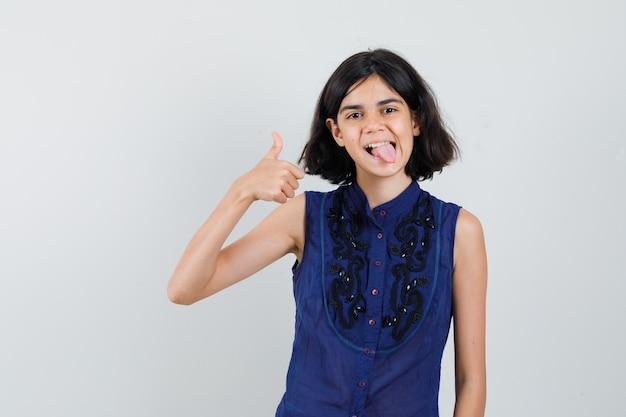 Kleines mädchen, das daumen oben zeigt, zunge in der blauen bluse herausstreckt und glücklich schaut.