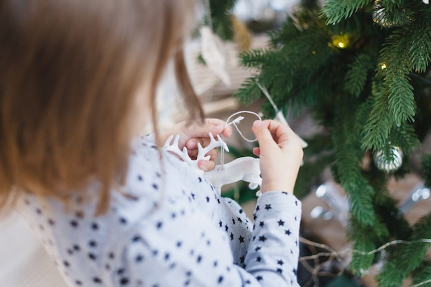 Kleines mädchen, das dekoration für weihnachtsbaum, weihnachtsinnenraum, vorbereitend für weihnachten und neues jahr, inneneinrichtung hält