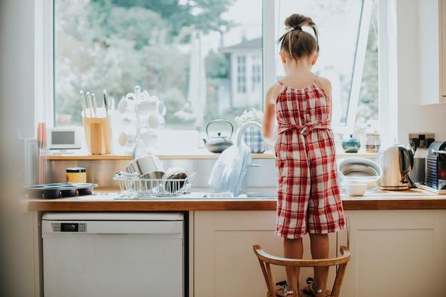 Kleines mädchen, das den abwasch macht
