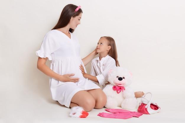 Kleines mädchen, das den bauch ihrer schwangeren mutter berührt und sie mit großer liebe ansieht
