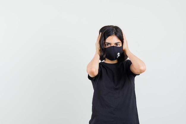Kleines mädchen, das den kopf mit den händen im schwarzen t-shirt, in der maske festhält und hilflos schaut. vorderansicht.