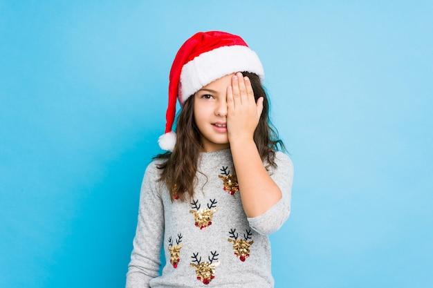 Kleines mädchen, das den weihnachtstag hat den spaß bedeckt die hälfte des gesichtes mit palme feiert.