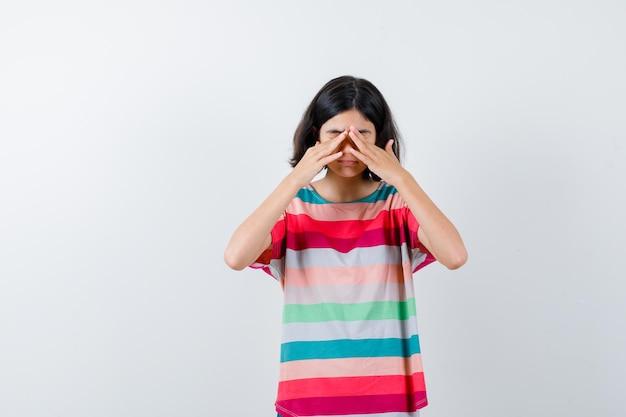 Kleines mädchen, das die augen mit den händen im t-shirt bedeckt und schläfrig aussieht. vorderansicht.