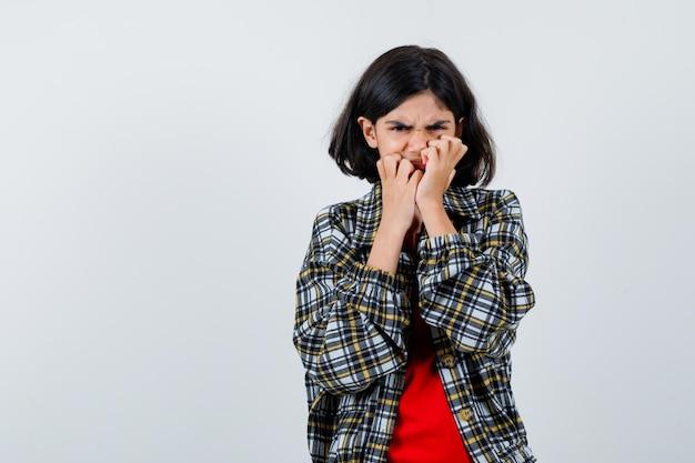 Kleines mädchen, das die hände am mund in hemd, jacke hält und unbequem aussieht, vorderansicht. platz für text