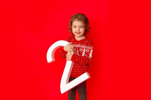 Kleines mädchen, das die nummer zwei in der winterkleidung auf einem roten hintergrund hält, raum für text