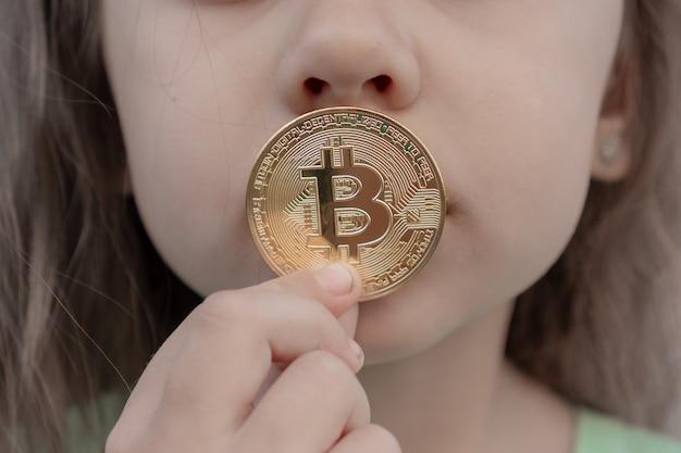 Kleines mädchen, das digitales bitcoin-geld hält